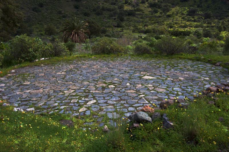 Mit Steinen gepflasterter Korndreschplatz beim Gehöft im Banamakrater