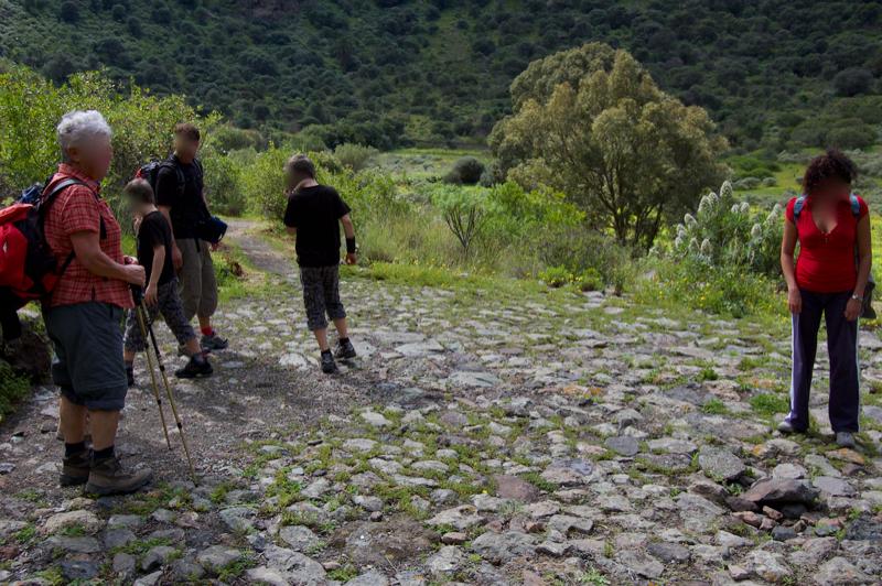 Wandergruppe auf einem steingepflastertem Korndrschplatz, Bandama Krater