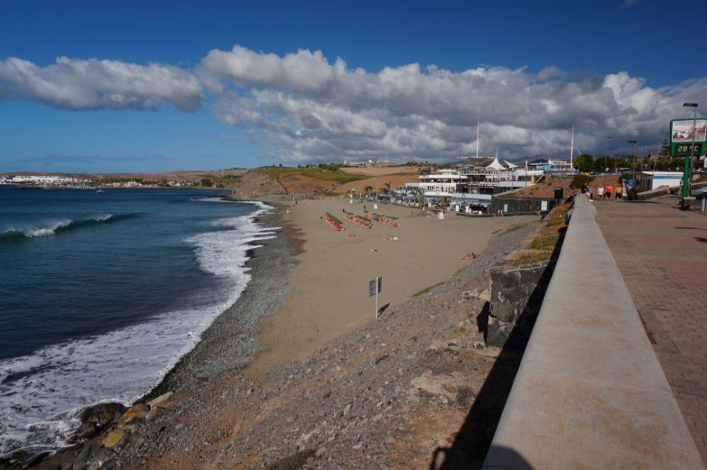 Strand von Meloneras mit Einkaufszentrum.