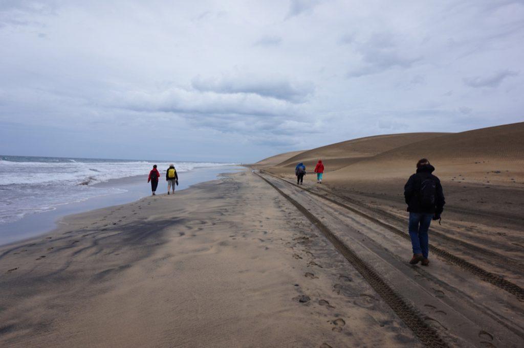 Dünen und Strand von Maspalomas mit Wanderern bei schlechtem Wetter.